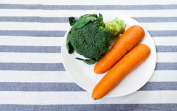 Broccoli and Two Carrots on White Plate Placed on White Striped Stock Photography