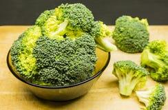 Broccoli in una ciotola su un fondo di legno Immagini Stock