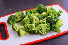 Broccoli on a white cutting board. On a grey abstract background. Step by step cooking Stock Photography