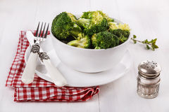 Broccoli on a white plate over white wooden background. Healthy organic broccoli on a white plate with table setting over white wooden background stock photo