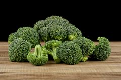 Broccoli on a wooden table isolated on a black. Background Royalty Free Stock Images