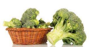 Broccoliflorets i en vide- korg som isoleras på vit Arkivfoto