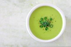 Broccolisoep in witte kom, luchtmening op wit graniet Stock Foto's