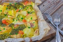 Broccoliwortelen, aardappels, witte ui en knoflook met de braadpan van het cheddarei in bakselschotel op houten achtergrond Hoogs royalty-vrije stock foto's