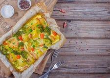 Broccoliwortelen, aardappels, witte ui en knoflook met de braadpan van het cheddarei in bakselschotel op houten achtergrond Hoogs stock foto's