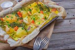 Broccoliwortelen, aardappels, witte ui en knoflook met de braadpan van het cheddarei in bakselschotel op houten achtergrond Hoogs stock afbeeldingen