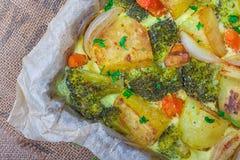 Broccoliwortelen, aardappels, witte ui en knoflook met de braadpan van het cheddarei in bakselschotel op houten achtergrond Hoogs stock fotografie