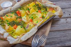 Broccoliwortelen, aardappels, witte ui en knoflook met de braadpan van het cheddarei in bakselschotel op houten achtergrond Hoogs stock afbeelding