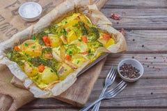 Broccoliwortelen, aardappels, witte ui en knoflook met de braadpan van het cheddarei in bakselschotel op houten achtergrond Hoogs royalty-vrije stock afbeelding