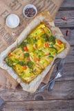 Broccoliwortelen, aardappels, witte ui en knoflook met de braadpan van het cheddarei in bakselschotel op houten achtergrond Hoogs royalty-vrije stock afbeeldingen
