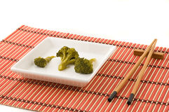 Broccolli dish with chinese chopsticks Royalty Free Stock Photography