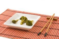 Broccolli dish with chinese chopsticks. On bamboo mat, studio shot Royalty Free Stock Photography