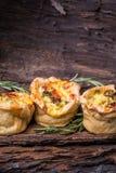 Broccolli tarts. Three broccolli tarts with cheese and rosemary on bark Royalty Free Stock Photo