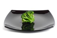 Broccolo su un piatto nero Fotografie Stock