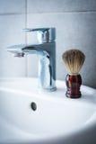 Brocha de afeitar en el lavabo en el cuarto de baño Foto de archivo libre de regalías