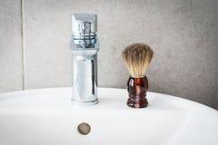 Brocha de afeitar en el lavabo en el cuarto de baño Foto de archivo