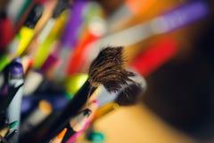 Brocha desaliñada en una caja de lápices coloreados Foto de archivo