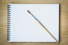 Brocha en el libro en blanco del papel de dibujo Fotografía de archivo libre de regalías