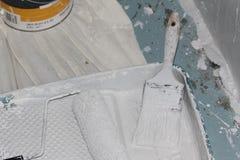 Brocha, rodillo de pintura, y bandeja de la pintura cubierta en la pintura blanca Fotografía de archivo