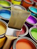 Brocha y latas multicoloras de la pintura Fotografía de archivo