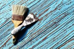 Brocha y paleta que raspan en la pintura de madera de la tabla por color ciánico Foto de archivo libre de regalías