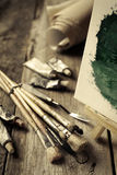 Brochas artísticas, tubos de la pintura de aceite y caballete Imagenes de archivo