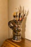Brochas de los artistas en jarro de la cerámica foto de archivo libre de regalías