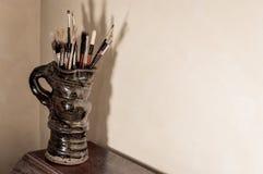 Brochas de los artistas en jarro de la cerámica Efecto envejecido fotos de archivo