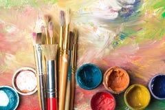 Brochas del artista y latas de la pintura de pintura encima Fotografía de archivo libre de regalías