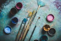 Brochas del artista y latas de la pintura de pintura encima Fotos de archivo libres de regalías