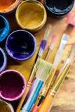 Brochas del artista y latas de la pintura de pintura encima Foto de archivo