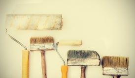 Brochas e imstruments de la pared para pintar en el fondo blanco, usados bien con el espacio de la copia para el texto fotos de archivo