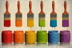 Brochas que gotean en los envases de la pintura Fotos de archivo