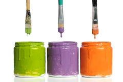 Brochas que gotean la pintura en los envases Imagen de archivo