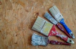 Brochas viejas en el panel de madera presionado Imagen de archivo libre de regalías