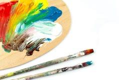 Brochas y colores en palet Imagen de archivo libre de regalías