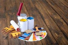 Brochas y latas de la pintura para la reparación en de madera Fotos de archivo libres de regalías