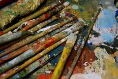 Brochas y paleta del artista en fondo imagen de archivo