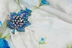 Broche azul del diamante artificial en una bufanda de seda blanca y azul, espacio de la copia Foto de archivo libre de regalías