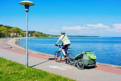 Broche de Curonian de station de vacances de Nida de bicyclette d'équitation d'homme et mer baltique photographie stock