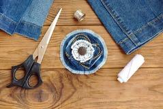 Broche de la flor de la mezclilla o accesorio azul del pelo Tijeras, hilo, dedal, aguja, vaqueros viejos en una tabla de madera D Imagen de archivo
