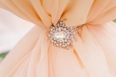 Broche de los diamantes en el satén amelocotonado como fondo Fotos de archivo libres de regalías