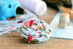 Broche de toile florale Broche de fleur de tissu décorée des perles, arme à feu de colle chaude, ciseaux, bobine de fil, dé, feui Photo libre de droits