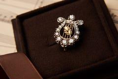 Broche del diamante bajo la forma de nota musical de una arpa en un regalo Imagen de archivo