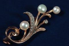 Broche del oro con las perlas en fondo azul marino Fotografía de archivo