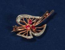 Broche del oro con los rubíes y los diamantes en fondo azul marino Foto de archivo