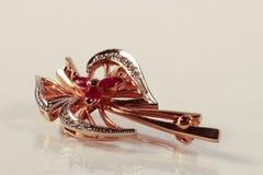 Broche do ouro com diamantes e rubis no fundo branco com re Fotografia de Stock Royalty Free
