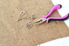 Broche, encantos do metal, anel de conexão, os alicates na serapilheira e fundo de madeira branco fotografia de stock