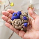 Broche feito a mão pequeno sob a forma de duas flores bege na palma de um close-up da mulher Fotografia de Stock Royalty Free