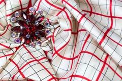 Broche roja del diamante artificial en una bufanda blanca y roja de la tela escocesa Imagen de archivo